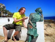 Please forgive me! A female statue looks thoroughly unconvinced as her human companion tri...
