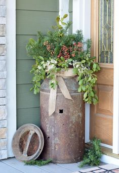 Old rusty milk jug turned into a planter. Lovely, rustic outdoor decor! Needs more bright red berries though. And more height in the greenery.