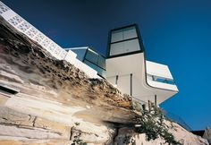 Looking out over the jagged cliffs of Dover Heights on the coast of Australia, features living and dining areas that cantilever out over the sea. The lower level is built into the rough stone walls of the cliff.