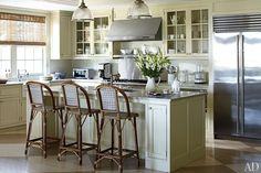Nantucket kitchen - The custom-made kitchen cabinetry by Thirty Acre Wood is painted in Benjamin Moore's Camouflage, while industrial-chic ceiling fixtures from Ann-Morris Antiques are suspended above the marble-top island. (July 2012)