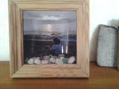 Valokuvan edessä samalta rannalta matkamuistoksi tarttuneita kiviä ja simpukoita sekä muutama rannan hioma lasinsiru