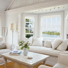 A cottage style living room gets an extra cozy window nook for napping, reading or relaxing. White slipcovered furniture and pillows make cleaning a breeze.