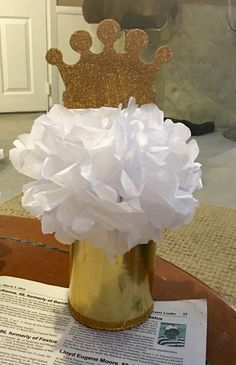 Centerpieces made from old formula cans, tissue paper, and small wooden crowns mod podged and glittered.