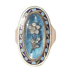 Fine quality high carat gold ring, circa 1790, the tapered shank terminating in a plaque of  powder blue guilloche enamel, surmounted by a diamond flower, under crystal. The plaque is within a border of  coloured enamels, with gold leaf decoration.