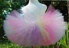 Hello Cutie 1 - This is the first of two Hello Kitty inspired tutus. The design is ballerina length, straight cut, with a sewn satin waistband. Five different tulle colors of citrine, pastel pink, pastel blue, bright pink, and purple were taken from a variety of Hello Kitty items recently found in retail stores. The bow in the back is handmade using pink Hello Kitty ribbon, rainbow ribbon which coordinates with the waistband, a pink flower, and hand applied rhinestones. By Enchanted Ever…