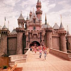 Children running through the gate of Sleeping Beauty's Castle at the opening day of Disneyland, 1955.