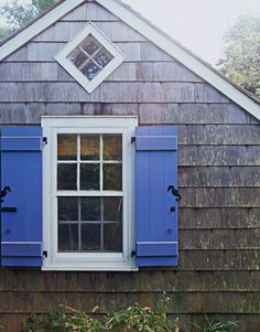 Gray weathered shingles with hydrangea blue shutters and crisp white trim are a classic Hamptons cottage combination. Klotz added the diamond-shaped window for architectural interest and more light.