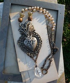Rustic french repousse Sacred Heart, adorned with antique paste rhinestones. A petite chandelier crystal swags beneath. The chain is comprised of vintage pearl rosary, box chain, brass floral caps, and hand carved olive wood beads from an old rosary.