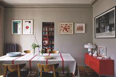 """La salle à manger, vers le bureau-bibliothèque qui s'ouvre par une petite ouverture comme une meurtrière. Au mur, à gauche, deux sérigraphies de papiers découpés d'Henri Matisse, à droite deux oeuvres de Sati Zech. Sur le buffet """"PS"""", Ikea, lampe Brumbury de Luigi Massoni pour iGuzzini, dessin de François Boisrond. Au mur, portrait d'Idriss Diabaté par François Bard."""