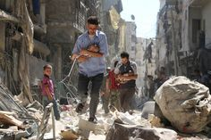 Syrian men carrying babies make their way through the rubble of destroyed buildings following a reported air strike on the rebel-held Salihin neighborhood of the northern city of Aleppo, on Sept. 11