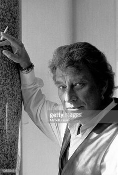 Posed portrait of French singer Johnny Hallyday smoking a cigarette in the Netherlands in 1994