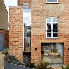 A sliver of glazing inserted between the back of this west London house and its brick extension is illuminated by lighting at night