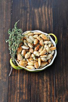 fried herbed almonds | 2 tablespoons extra-virgin olive oil, 2 cups whole blanched almonds, 2 tablespoons fresh thyme, Coarse salt and freshly ground pepper.