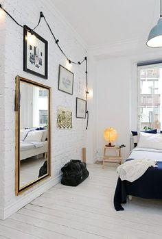 Briques peintes en blanc, tableaux, miroir doré, guirlande... Inspiration salon / White walls, art, golden mirror, light bulbs... what a lovely living room it could be!