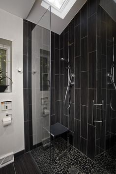 black tile bathroom wall connected by black bathroom seat and stainless steel shower on the wall
