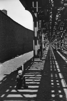 """.Illinois. Chicago. 1947. """"A child playing baseball alone beneath the Elevated. Probably my expression was just as strange as his, for I certainly didn't expect to see a human being here"""" - Photo & comment HCB"""