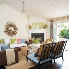 An effective room arrangement starts with the focal point, the cornerstone of your living room design. Typically a fireplace plays this role, but in this contemporary cottage space, the view out the French doors takes center stage instead. Orient the main seating piece toward the focal point and arrange the secondary seating pieces around the main piece. In winter, the room could be rearranged to focus on the fireplace.