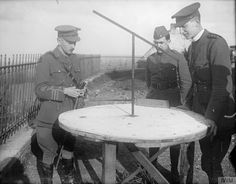 British and American officers examining a German artillery range table found in the observation station on top of Mont St. Aubert, 13 November 1918.