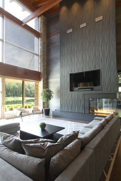 High ceilings, expansive windows, and a fun fireplace design make this living room a great place to sit back and relax. | to see more of the project, visit http://studioduo.net