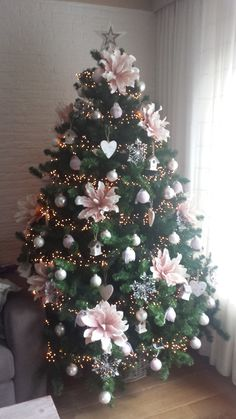 Elegant Christmas tree decorated with big pink flowers and silver ornaments.
