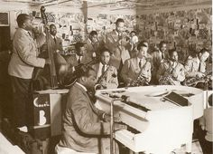 The Count Basie Band (1938) During its triumphant summer long 1938 residence at the Famous Door. Left to right: Walter Page, Jo Jones, Freddie Green, Benny Morton, Basie himself, Herschel Evans, Buck Clayton (who entirely obscures Dan Minor), Dicky Wells, Earle Warren (who mostly obscures Ed Lewis), Harry 'Sweets' Edison, Jack Washington, and Lester Young.