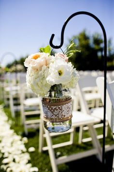 white and blush ceremony flowers in a mason jar with burlap and lace.