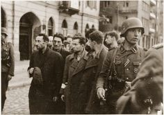 """SS troops guard members of the Jewish resistance captured during the suppression of the Warsaw ghetto uprising. The original German caption reads: """"Bandits!"""