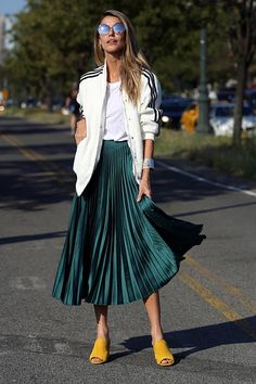 Dark green pleated skirt with white shirt and blazer and yellow shoes