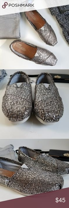 TOMS Metallic Glitter Wool Slip On Flats Nubby metallic weave updates TOMS classic slip-on flats with cozy texture and decadent shine.  ·         Round toe; slip on  ·         Elasic goring at instep; cushioned insole for comfort  ·         Metallic-flecked woven wool, cotton lining, rubber and textile sole  Never worn Toms Shoes Flats & Loafers