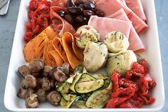 Artfully place cold cuts of meat and marinated vegetables on a beautiful platter then let everyone dig in.
