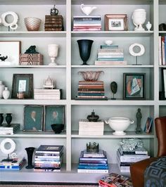 Displaying treasures of similar colorway in various heights and shapes with book spines facing the viewer is one of those suprises found in a well decorated room.