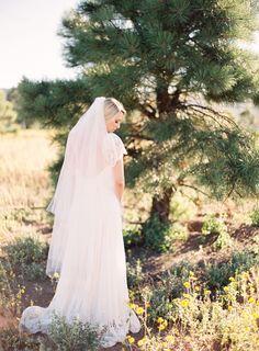 Pretty boho bride with a lace Rue de Siene dress and long veil.