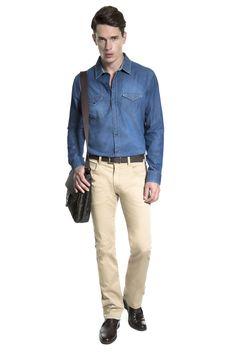 Camisa jeans lavada, calça khaki slim, cinto e bota de couro café e pasta messenger para dar um toque moderno à produção.