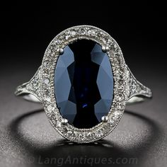 A deep, dark and mysterious midnight blue oval sapphire, weighing 3.50 carats, is enshrined in a masterfully handcrafted platinum and diamond mounting dating from the Edwardian/early-Art Deco design period - circa 1910~early-1920s. The dusky gemstone fills a glittering diamond frame supported by matching diamond-set shoulders and an exquisitely detailed, decorative under gallery. Delicate hand engraved milgraining adds the finishing touch to this exemplary antique jewel.