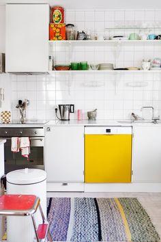 """Funkisköket producerades av Apparat under en period. Luckorna är lackade i """"kommunalgrått"""" och har retrohandtag och ljus bänkskiva av carraramarmor. Hyllplan och konsoler är från samma produktion, liksom kökskåpan som döljer en inbyggnadsfläkt. Diskmaskinens front är lackad i solgult med slät lackeringsroller. Spisen är av märket Bosch, undermonterad diskho kommer från Intra och kranen är från Vola. Kakelplattorna är vita standardplattor, 15x15 cm. Vägglampor från Ifö Electric."""