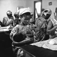 ca. 1957, Leopoldville, Belgian Congo --- A woman knitting a jumper for her baby, asleep on her lap, during a government training session in parenthood at Leopoldville in the Belgian Congo. --- Image by ? Hulton-Deutsch Collection/CORBIS