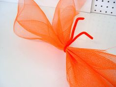 Tutorial demonstrating how to make a Deco Poly Mesh Flower with Orange Deco Poly Mesh Netting and Pencil Ties with Balls