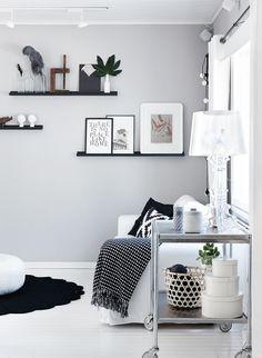 Tv-huoneen takaseinää koristavat harmaa tapetti ja kauniisti toteutettu seinäasetelma. Teräksinen tarjoiluvaunu on pelastettu roskalavalta. Bloomingvillen tekstitaulu on Suvimarja-lifestylepuodista.