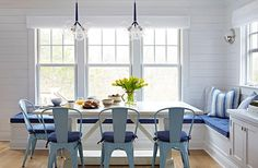 White shiplap walls frame windows dressed in white roman shades positioned above and L-shaped built-in banquette topped with a blue tufted cushion and blue striped accented pillows.