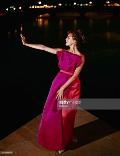 Aproned for evening...Designer Forquet of Italy puts an apron on the lady in the evening. Silhouetted against the picturesque background of the River Arno and the bright lights on the Ponte Vecchio in Florence. This evening creation, for Fall 1963, is brilliantly portrayed in orange and fuchsia heavy satin. The designer tops an orange tube-shaped gown with a fan-shaped overlapping panel on the front, which creates an apron effect.