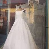 For sale is a beautiful designer wedding dress by Suzanne Neville Lady; the dress is a small size 2. Made of a stunning zibeline silk in white ivory. It has a boned bodice (no need for uncomfortable bras!) and a white ivory ribbon that goes around the waist, with a full skirt and train. The skirt has net underskirts with one that is removable to support it and give it a bit of body with a two tier gather at the back before the full train. The back of the dress has little ivory silk buttons…