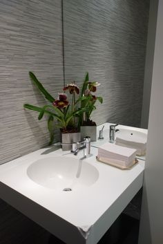 Fresh lady slipper orchids add a natural touch to a modern bathroom.