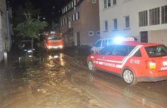 Feuerwehrkräfte versuchen nach einem Starkregen in Pfullingen (Baden-Württemberg) eine überschwemmte und verschlammte Straße zu reinigen.