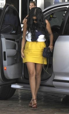 Kourtney Kardashian wearing Yves Saint Laurent Brown Tribute High Heel Leather Sandals, Chanel Vintage Sack Bag in Blue Plain Leather, Chloe Printed Cropped Sleeveless Blouse and Mustard Yellow Fitted Mini Skirt.