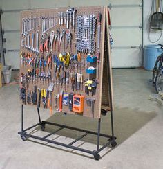 Garage: DIY rolling tool cart | Unclutterer. This would work great in a craft room also. Hooks for hanging bead strings. Peg board baskets for items. Repurpose soup cans for marker or brush holders. #StorageMart #OrganizeIt