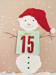 What a cute and fun way to count down the days until Christmas. I love snowmen! Wouldn't it be fun to have the children make these. If you don't have craft paper you could use the inside of a brown paper bag, or colored paper. The children each paint their own snowman, and even use scraps of fabric for his hat & small twigs for his arms. Depending on their ages, they can help with writing the numbers, punching holes, or tying the numbers on.