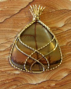 This pendant is pretty as a picture with its sophisticated wire wrapping and subtle but eye-catching stone. The triangular shape gives the design