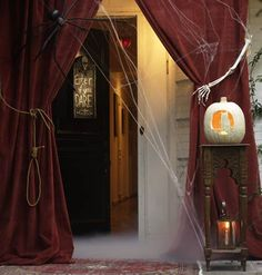 Red Velvet Entrance  Red velvet curtains swept with spiderwebs frame the front door in a theatrical welcome. Roll out a magic carpet to transport guests to the fantastic terrors beyond.