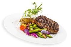Angus steak - beef steak on hot salad made of asparagus, red onion and bacon served with baked potato and garlic cottage cheese