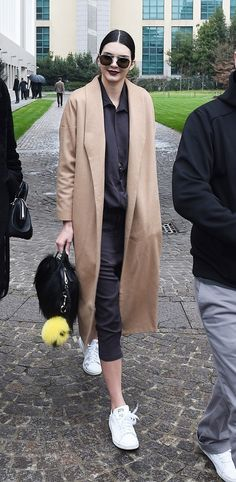 Kendall Jenner wears a black silk shirt, cropped pants, a camel coat, Stan Smith sneakers, a furry Givenchy bag, and aviator sunglasses